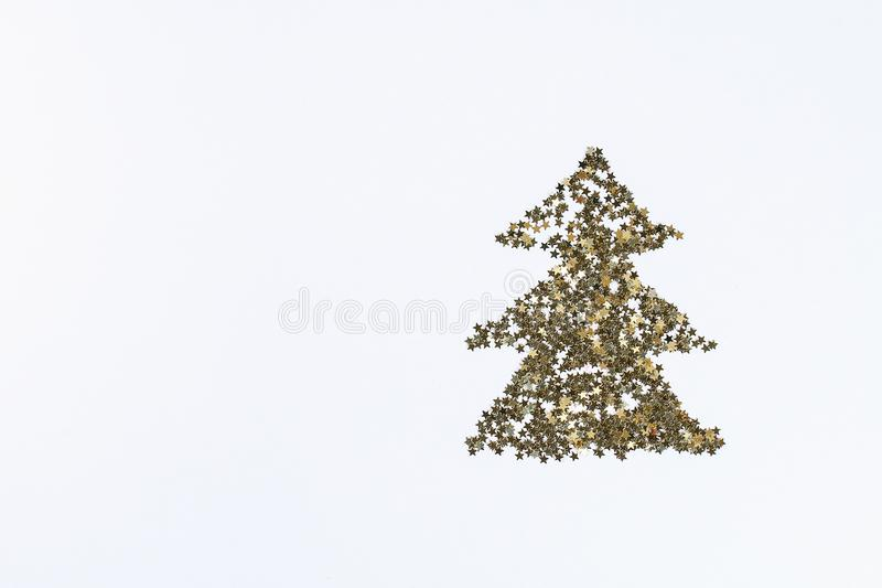 Christmas layout. Golden confetti in the form of stars folded in the shape of Christmas tree on white background. New Year 2019, royalty free stock photos