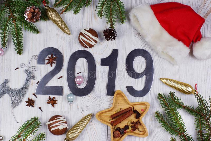 Christmas layout with numbers 2019, Santa hat, decorations and Christmas tree branches on a light wooden background. royalty free stock photography