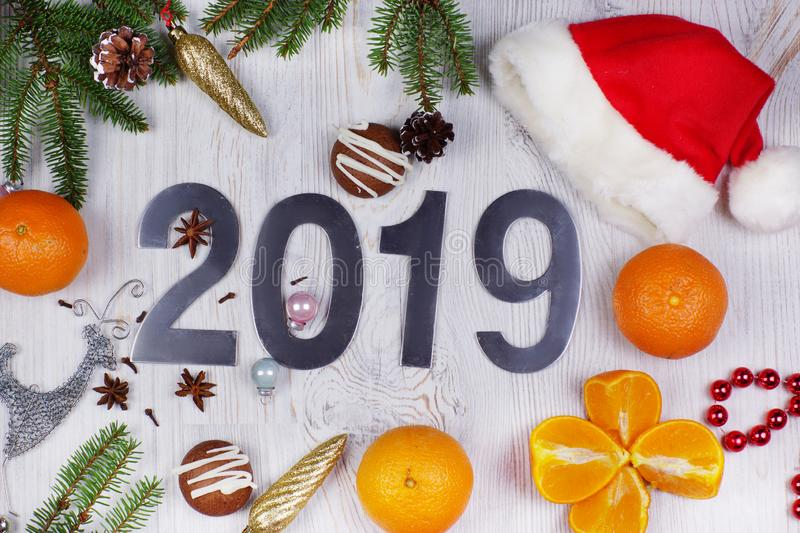 Christmas layout with numbers 2019, Santa hat, decorations and Christmas tree branches and tangerines on a light background stock image