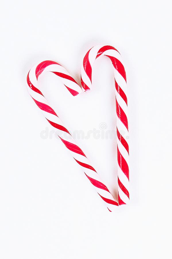 Christmas layout. Striped red-white cane candies on a white background. New Year 2020, christmas stock photos