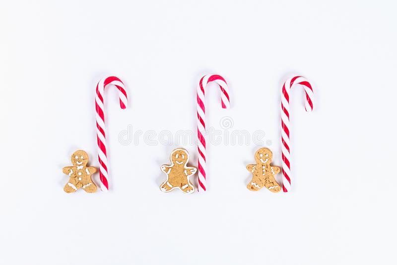 Christmas layout. Striped red-white cane candies and homemade ginger cookies on a white background. New Year 2019, christmas, royalty free stock photography