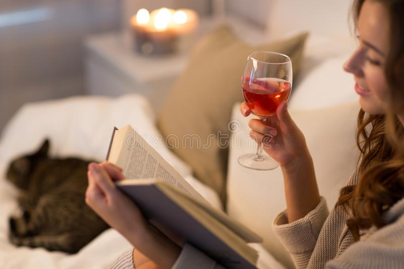 Happy young woman reading book in bed at home stock images