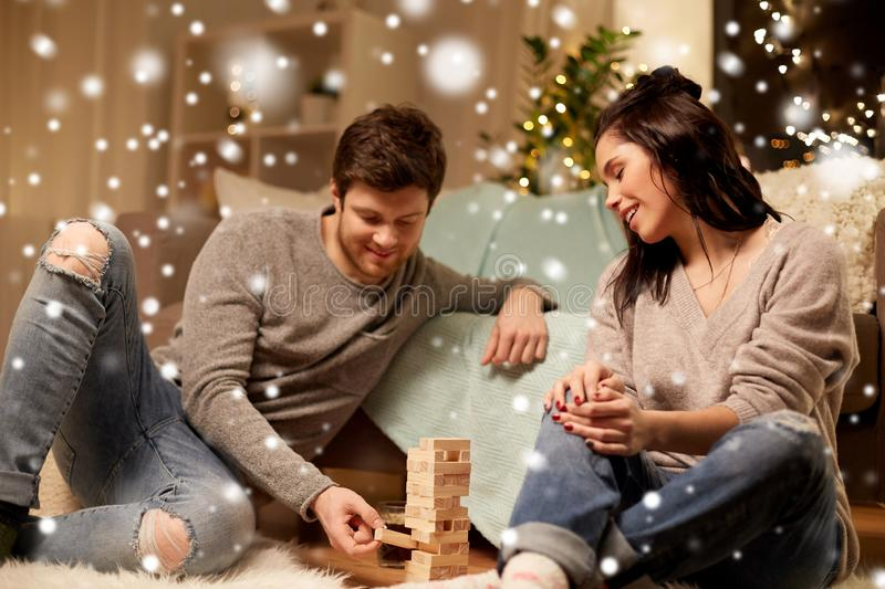 Happy couple playing block-stacking game at home stock image