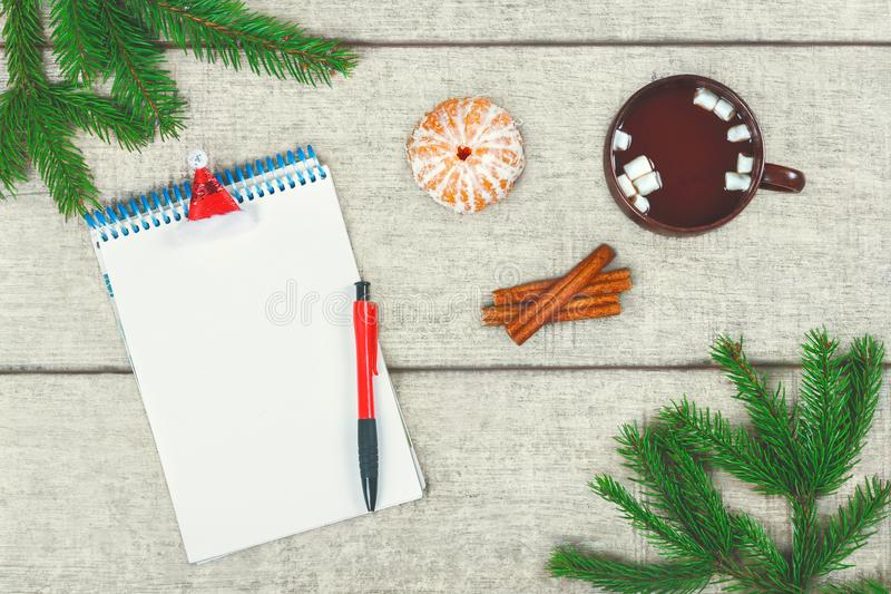 Christmas letter. Cup of hot coffee with cinnamon and marshmallow, tangerine, fir branches and pine cone. royalty free stock photos
