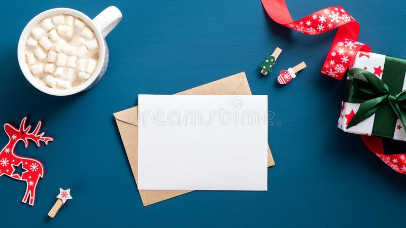 Christmas letter over blue background. Flat lay blank paper card, craft paper envelope, coffee cup, festive Xmas decorations, gift royalty free stock image