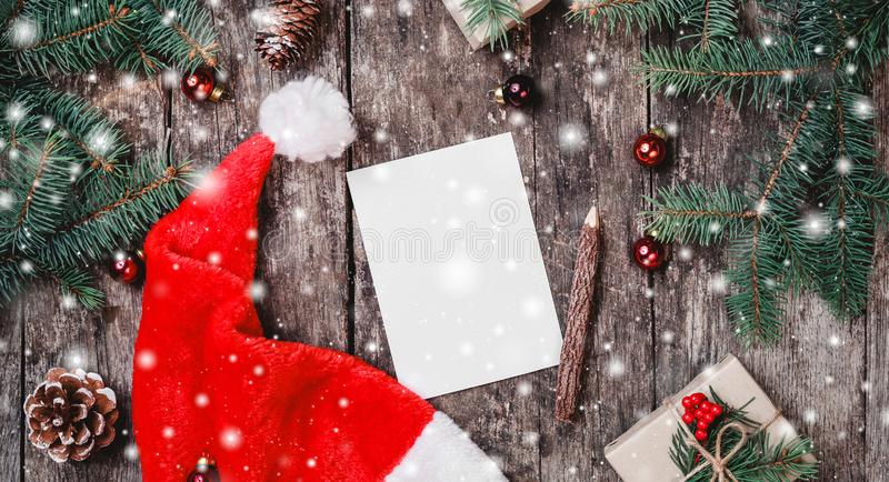 Christmas letter on wooden background with red Santa hat, Fir branches, pine cones, red decorations. Xmas and Happy New Year. Composition. Flat lay, top view stock photo