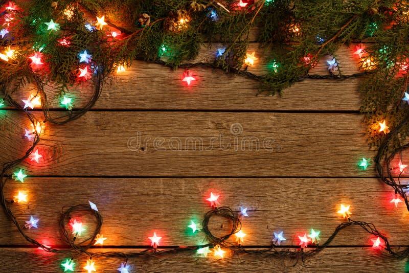 Christmas lights border on wood background stock image