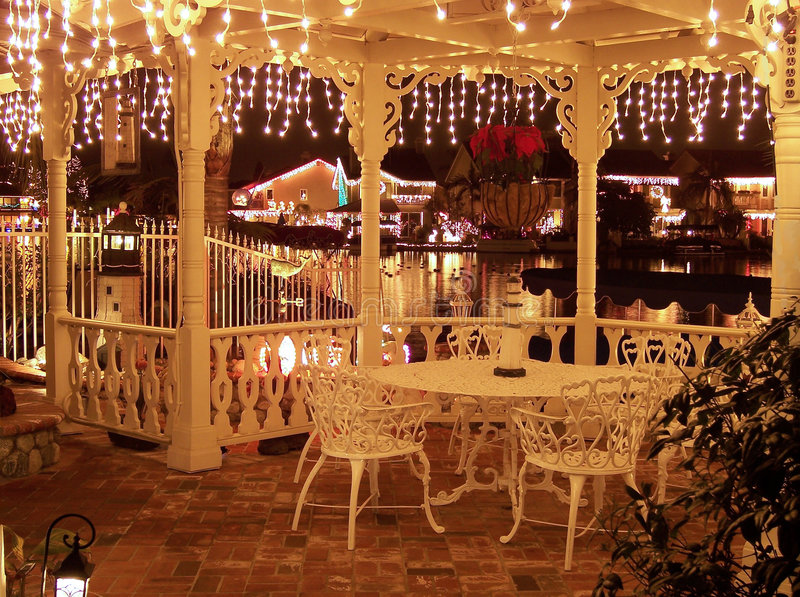 Christmas Lights Decorated Gazebo Overlooking a Reflective Lake royalty free stock photo