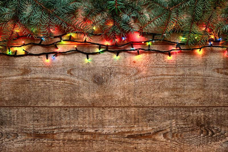 Christmas lights and fir tree branches on wooden background. New Year festive decorations with colorful glowing stock images