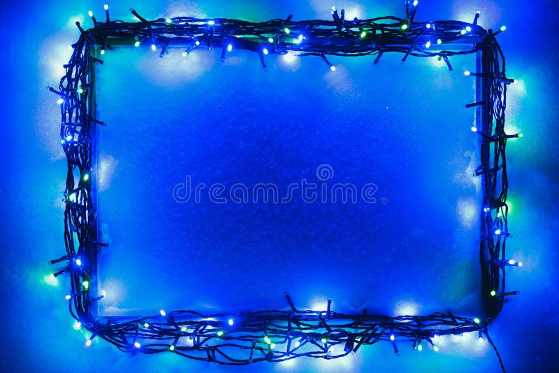 Christmas lights frame on snow background stock photos