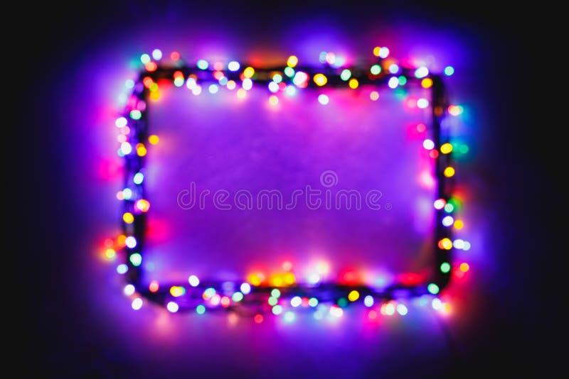 Christmas lights frame on snow background, purple color stock image