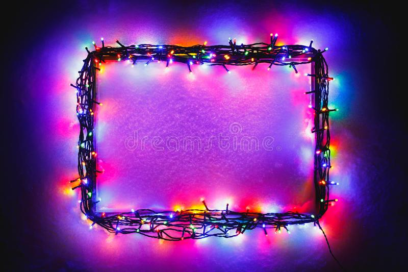 Christmas lights frame on snow background stock photography
