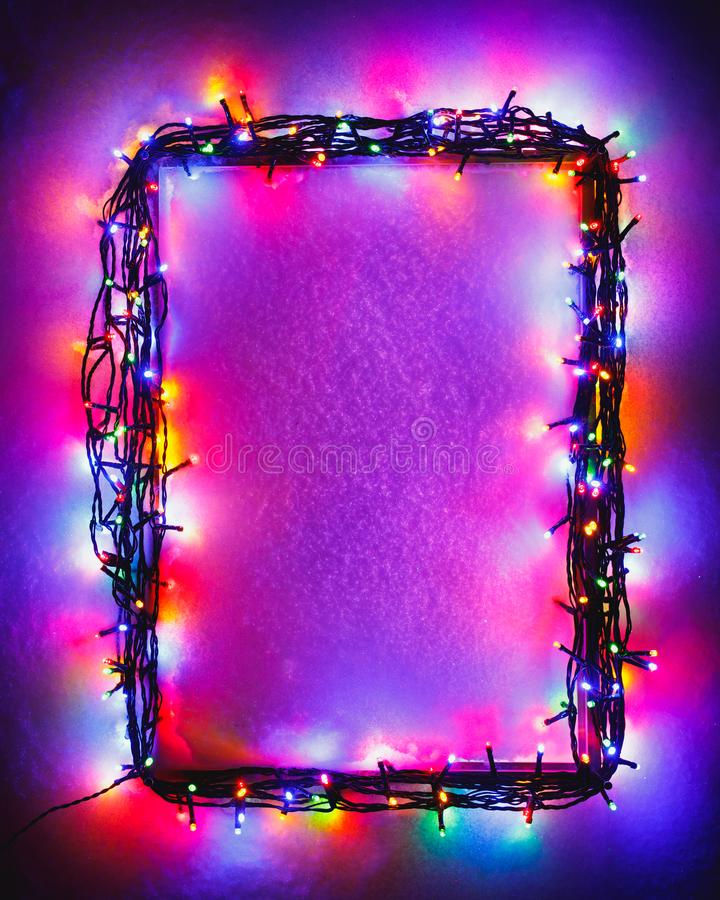 Christmas lights frame on snow background, purple color royalty free stock photo