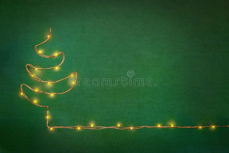 Christmas lights garland arranged like christmas tree over green background. Flat lay, copy space. stock photo