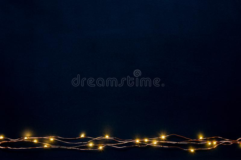 Christmas lights garland border over black background. Flat lay, copy space. stock image