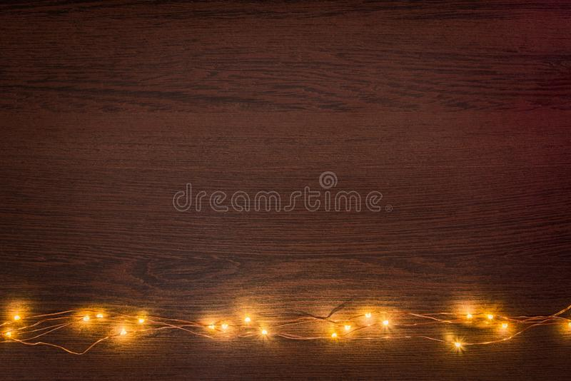 Christmas lights garland border over dark wooden background. Flat lay, copy space. Christmas lights garland border over dark wooden background. Flat lay, copy royalty free stock images