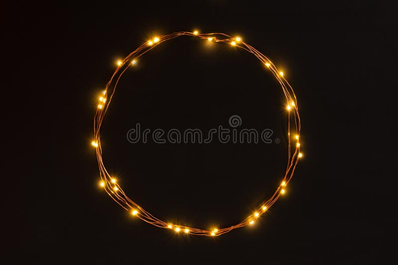 Christmas lights garland circular border over black background. Flat lay, copy space. Christmas lights garland circular border over black background. Flat lay stock images