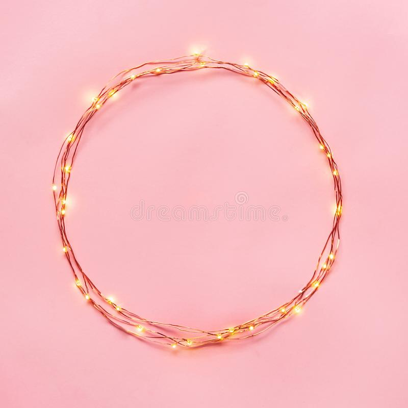 Christmas lights garland circular border over pink background. Flat lay, copy space. stock photo