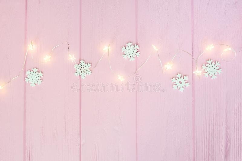 Christmas lights garland with snowflakes border over pink wooden background. Scandinavian flat lay, copy space stock photography
