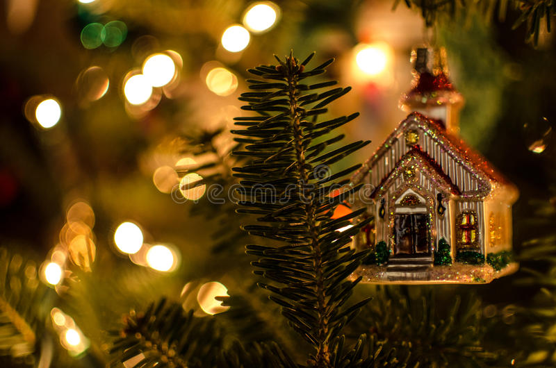 Christmas Lights Glimmering with ornament. Christmas lights glowing in background with Church ornament in front royalty free stock photography