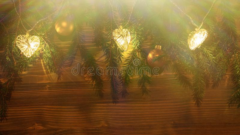 Christmas lights and ornaments on branches of a Christmas tree on a dark wooden background stock image