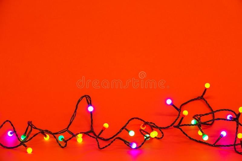 Christmas lights over red background. Colorful border royalty free stock image