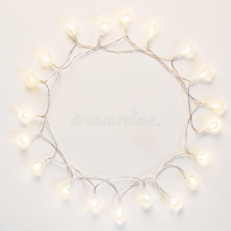 Shining christmas lights round frame with copy space on white background stock photo