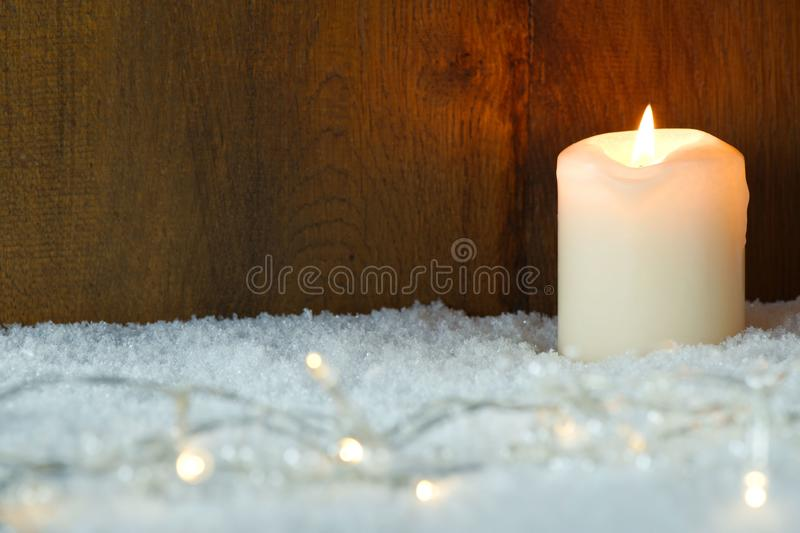 Christmas lights in snow. Burning candle with Christmas lights in snow stock photo