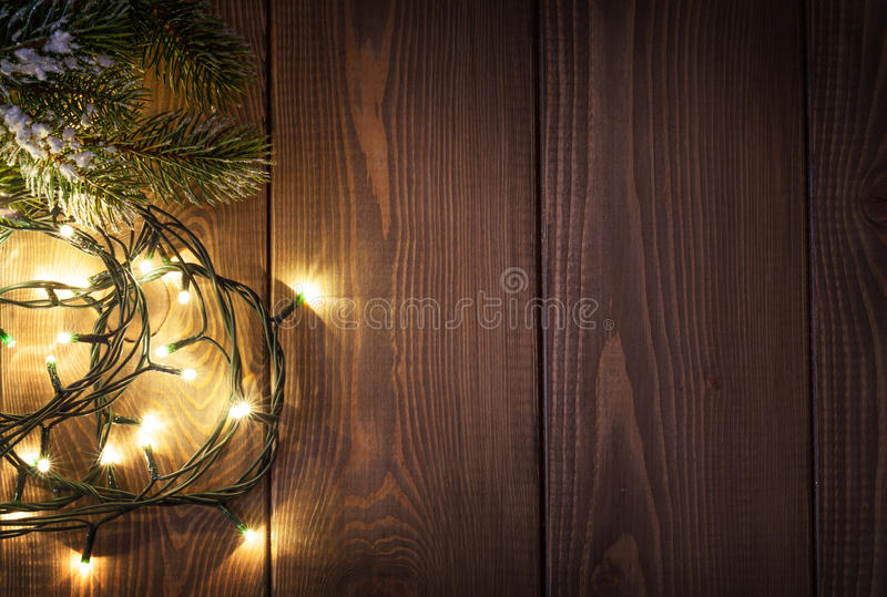 Christmas lights and snow fir tree. Over wooden background with copy space stock photos