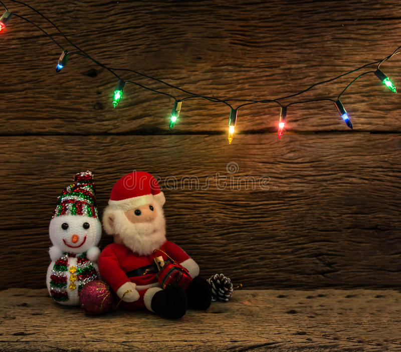 Christmas lights with snow man and santa claus doll on wood bac. Kground royalty free stock photo