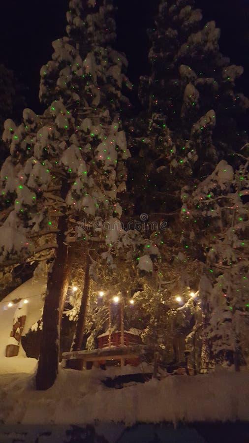 Christmas lights. Star shower Christmas lights on snow covered cabin royalty free stock image