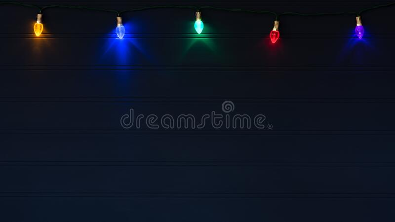 Christmas Lights on String Glowing against a Dark Navy Blue Wood Board Background with Copy Space below with a horizontal crop. It`s has room for your words stock photos