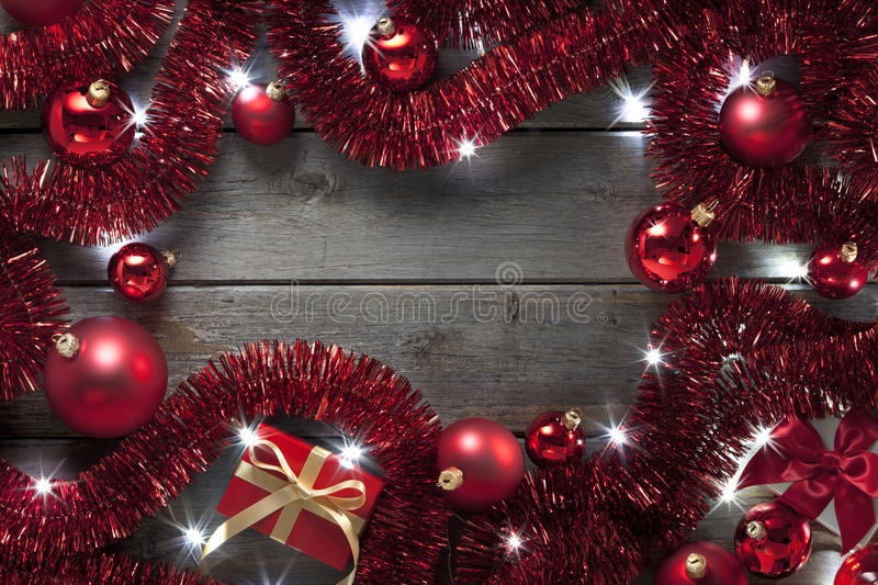Christmas Lights Tinsel Background. A background of Christmas presents, red tinsel, ornaments and fairy lights on a rustic wood background