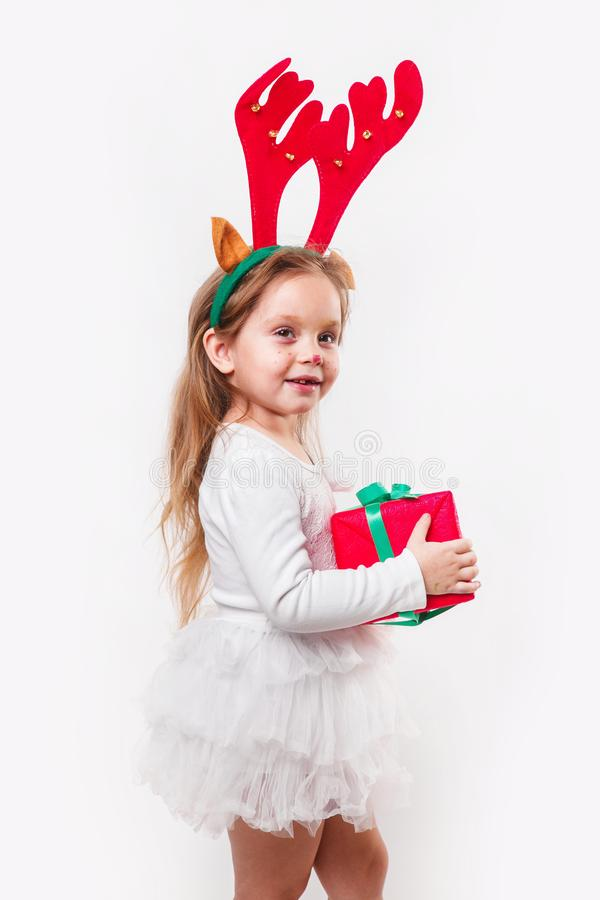 Christmas little baby in deer horns holding a red present box on white background. Christmas time royalty free stock image