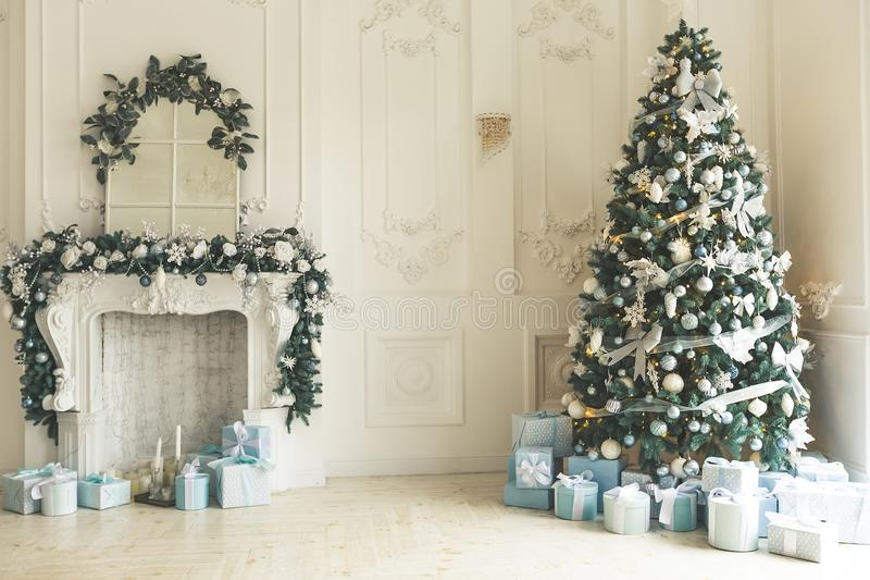 Christmas living room with a Christmas tree, fireplace, gifts and a large window. Beautiful New Year decorated classic home interi stock photos
