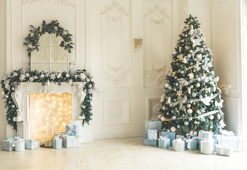Christmas living room with a Christmas tree, fireplace, gifts and a large window. Beautiful New Year decorated classic home interi stock photo