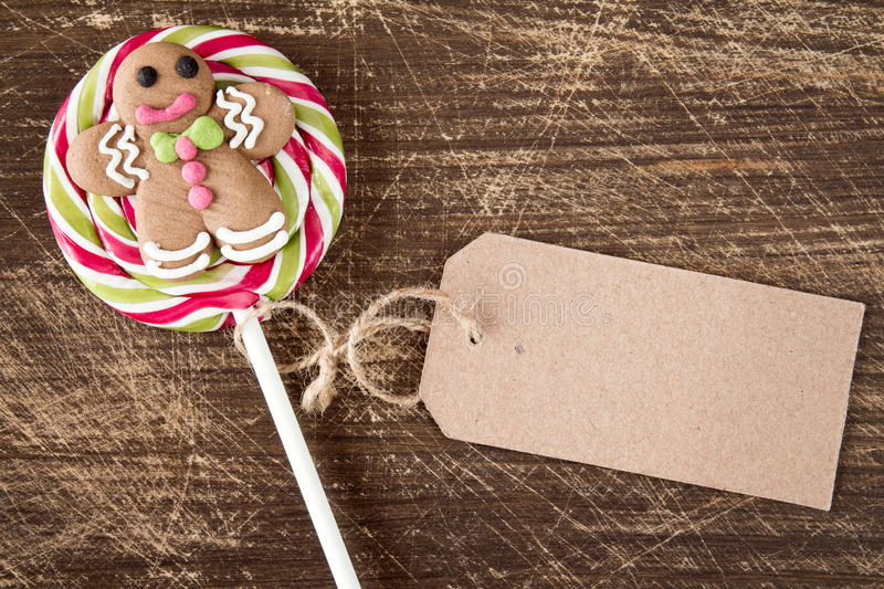 Christmas lollipop with gingerbread man. And blank price tag on wooden background royalty free stock photos