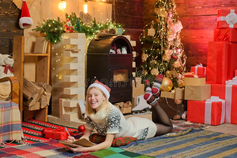 Christmas magic concept. Happy winter holidays at cozy decorated home with family. Teenage blonde girl in knitted. Sweater dress and red hat writing a wish list stock image
