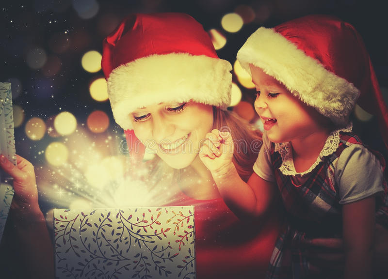 Christmas magic gift box and a happy family mother and daughter baby girl. Christmas magic gift box and a women happy family mother and daughter baby girl stock photos