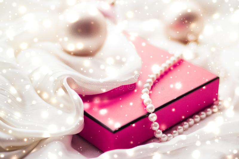 Christmas magic holiday background, festive baubles, pink vintage gift box and golden glitter as winter season present for luxury stock photography