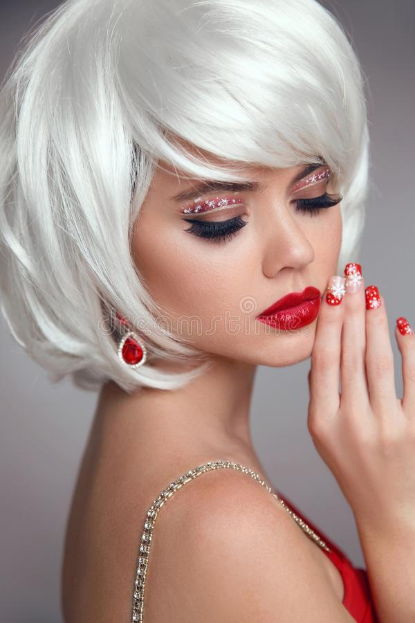 Christmas makeup. Red lips Makeup. Beautiful blond closeup portrait. Manicured nails. Jewelry. White Short bob hairstyle. Sensual royalty free stock image