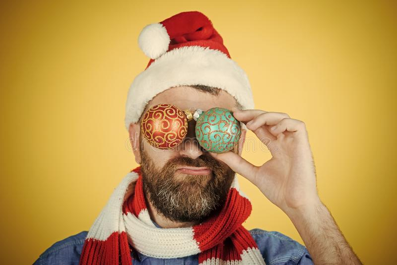 Christmas man cover eyes with xmas balls on yellow background. Spirit, joy, peace concept. Unhappy hipster in santa hat and scarf. Holiday decorations and royalty free stock photography