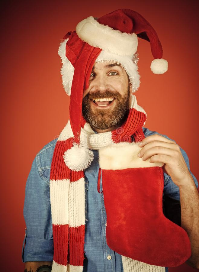 Christmas man hold xmas sock. Hipster in santa hats, scarf smile on red background. New year, winter holidays celebration. Gift or present concept royalty free stock photo