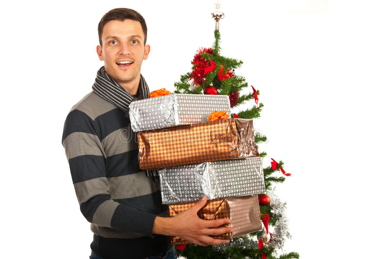 Christmas man holding stack of gifts. Happy Christmas man holding stack of gifts in front of tree royalty free stock photo