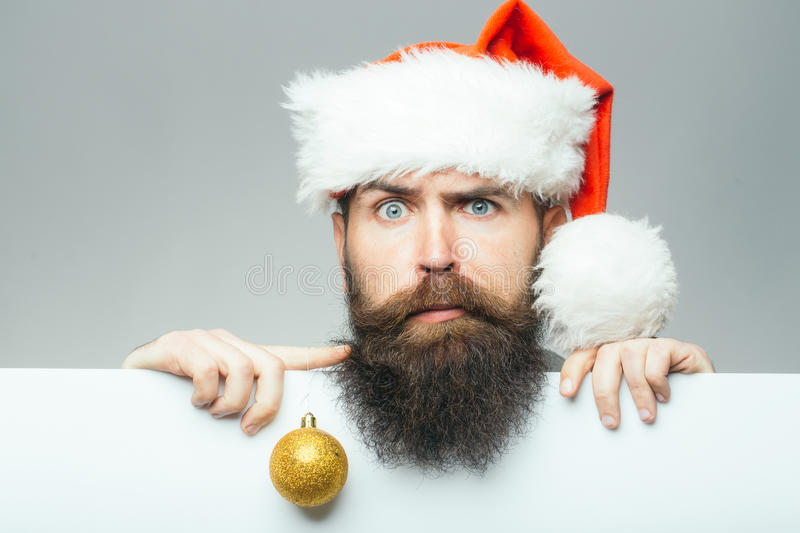 Christmas man with paper sheet. Handsome bearded man with long lush beard and moustache on surprised face decoration ball in christmas hat with paper sheet on stock image