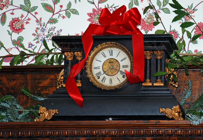 Christmas Mantel Clock. An antique mantel clock decorated for Christmas with pine boughs and a red ribbon stock photo