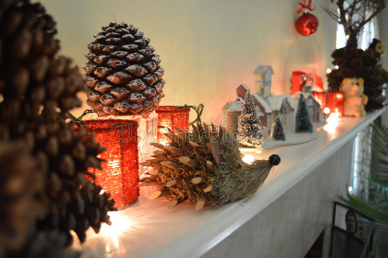Christmas mantel decorations. A white mantel shelf decorated with pine cones, hedgehog, snow covered house, candles, teddy bear, hanging ball and red jug or ( stock photo