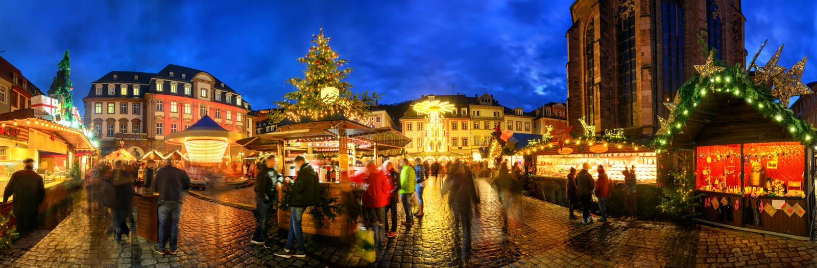 Christmas market in Heidelberg, Germany. A panorama shot at dusk showing illuminated kiosks, architecture and blurred people royalty free stock photography