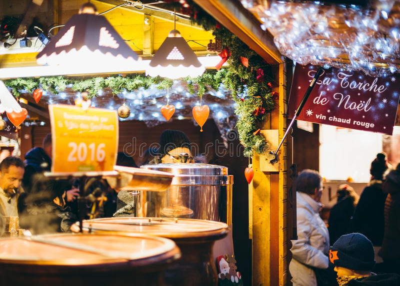 Christmas Market stall selling traditional hot french wine mulled wine. STRASBOURG, FRANCE - DEC 20, 2016: Customers drinking hot Christmas wine at the stock images