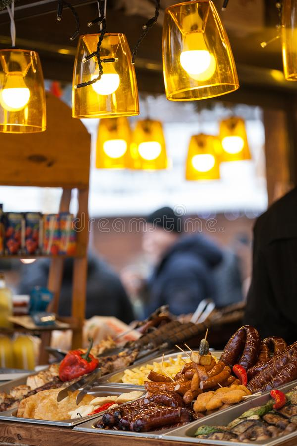 Christmas markets in Lviv. Grilled vegetables, sausages and meat sale on street market royalty free stock images